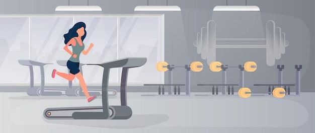Großes fitnessstudio. mädchen läuft auf einem laufband. frau, die auf dem simulator in der turnhalle läuft.