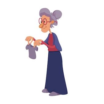 Großmutter, die flache karikaturillustration der kinderkleidung hält. fröhliche oma. ältere frau. gebrauchsfertige 2d-zeichenvorlage für werbung, animation und druckdesign. isolierter comic-held