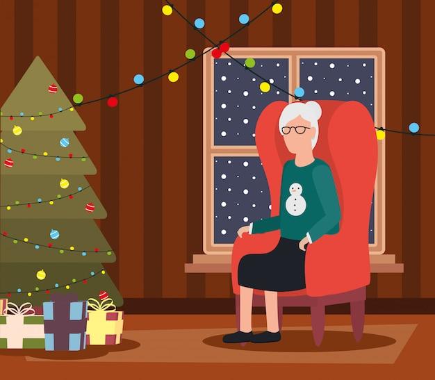Großmutter im wohnzimmer mit weihnachtsdekoration