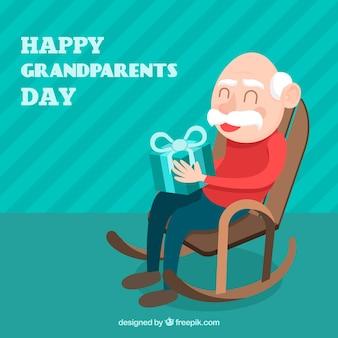 Großvater hintergrund sitzt mit einem geschenk