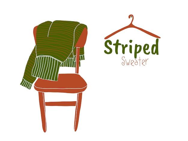 Grüne gestreifte strickjacke auf dem braunen stuhl
