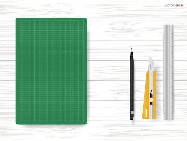 Grüne schneidematte mit stationärem objekt auf weißem holzhintergrund