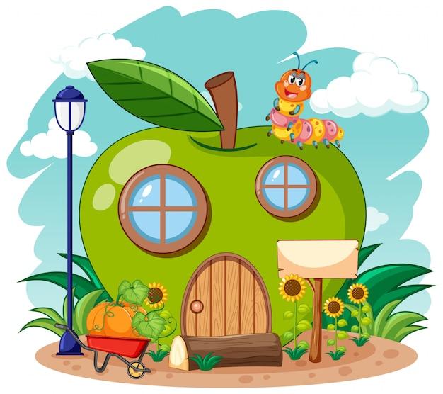 Grünes apfelhaus und niedlicher wurm im gartenkarikaturstil auf himmelhintergrund