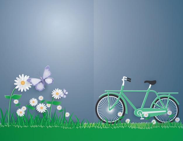 Grünes fahrrad auf dem gras und dem purpurroten schmetterling