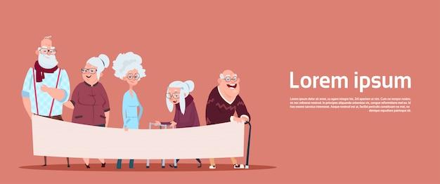 Gruppe ältere leute, die leere fahne mit kopienraum halten modernen großvater und großmutter in voller länge