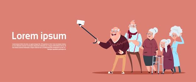 Gruppe ältere leute, die selfie-foto mit selbststock-modernem großvater und großmutter machen