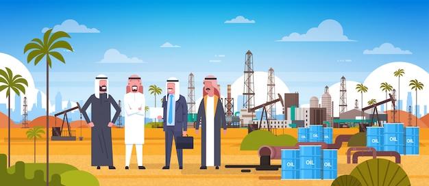 Gruppe arabische geschäftsleute auf bohrinsel im wüsten-osttreibstoffproduktions-und handels-konzept