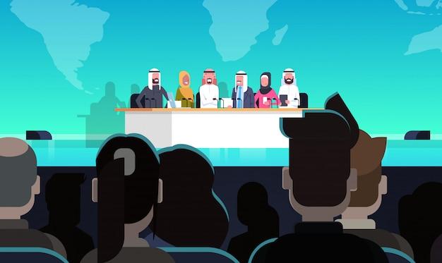 Gruppe arabische geschäftsleute auf konferenz-öffentlichem debatten-interview-konzept-offizieller sitzung von arabischen politikern vor großem publikum
