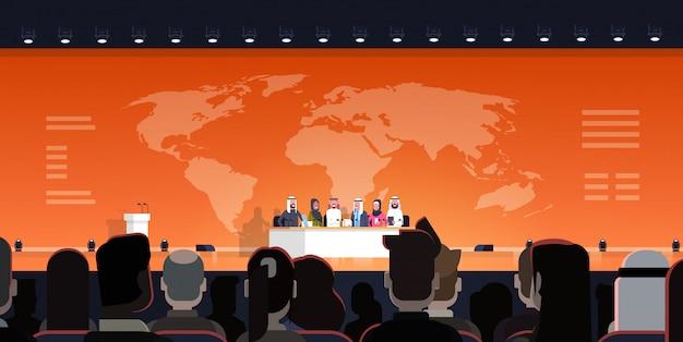 Gruppe arabische geschäftsleute auf konferenz-öffentlichem debatten-interview über weltkarteabbildung amtlicher sitzung der arabischen politiker