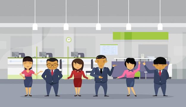 Gruppe asiatische geschäftsleute, die anzüge im modernen büro tragen