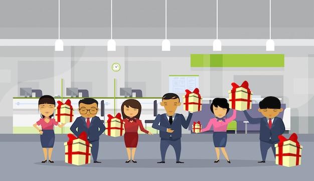 Gruppe asiatische geschäftsleute halten geschenkboxen im modernen büro