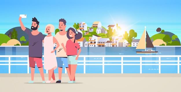 Gruppe der jungen leute, die selfie-foto auf smartphone-kamerafreunden machen, die zusammen bergstadtinsellandschafthintergrund-urlaubsreisekonzept in voller länge horizontal stehen