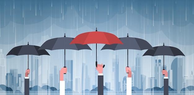 Gruppe hände, die regenschirme über sturm im stadt-enormen regen-hintergrund-hurrikan-tornado im stadtnaturkatastrophen-konzept halten