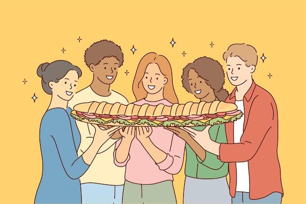 Gruppe junger internationaler multiethnischer freunde afroamerikanischer frauenmänner, die großes sandwich zusammen teilen