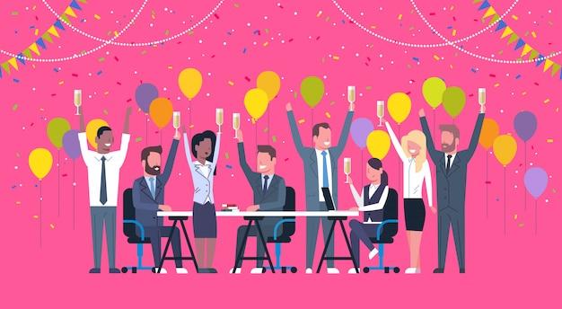 Gruppe nette verschiedene geschäftsleute feier-erfolgs-glückliches mischungs-rennen team hold raised hands sitting am verzierten schreibtisch