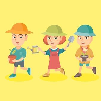 Gruppe von drei kaukasischen kindern, die blumen pflanzen