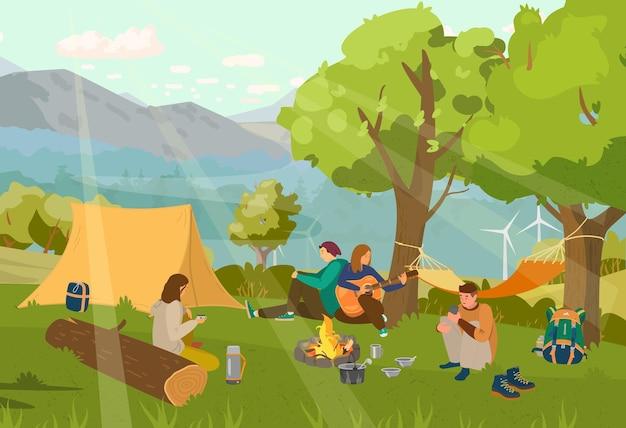 Gruppe von freunden auf dem campingplatz, der am lagerfeuer sitzt und gitarre spielt.