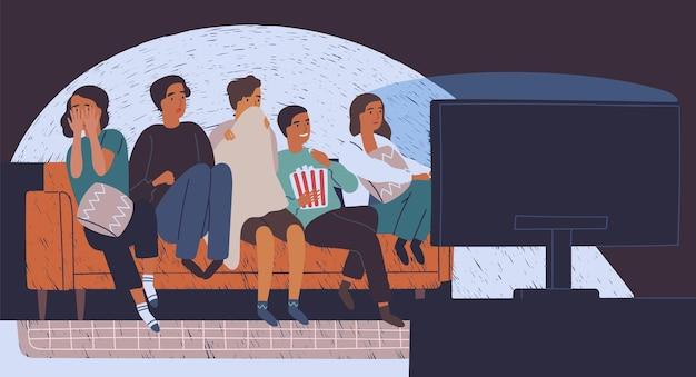 Gruppe von freunden, die auf dem sofa in der dunkelheit sitzen und horrorfilm schauen