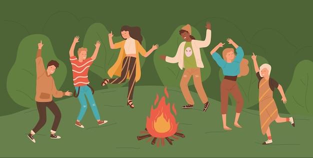 Gruppe von glücklichen jungen männern und frauen, die um lagerfeuer im wald tanzen.