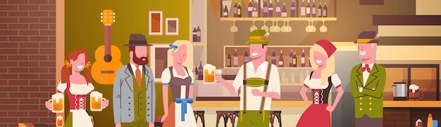 Gruppe von personenen-getränk-bier im bar-oktoberfest-parteifeier-mann und frau, die fest-konzept der traditionellen kleidung trägt