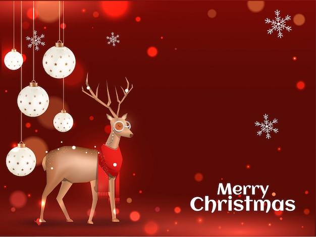 Grußkarte der frohen weihnachten mit tragendem schal, schneeflocken und hängendem flitter des goldenen rens verziert auf roten bokeh lichteffekt.