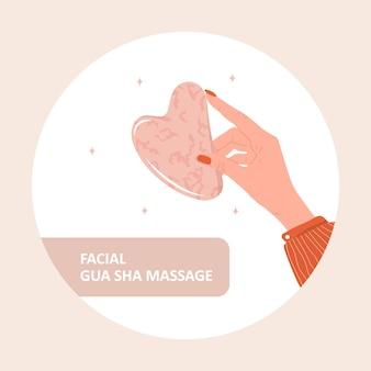 Gua sha schaber für gesichtsmassage. weibliche hand, die natürlichen rosa quarzstein hält.