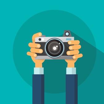 Hände, die foto-kamera-flaches design halten