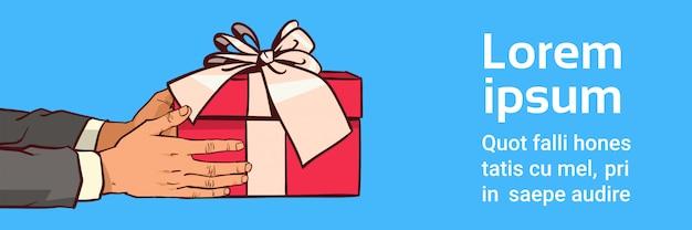Hände, die rote geschenkbox mit band-bogen auf schablone halten