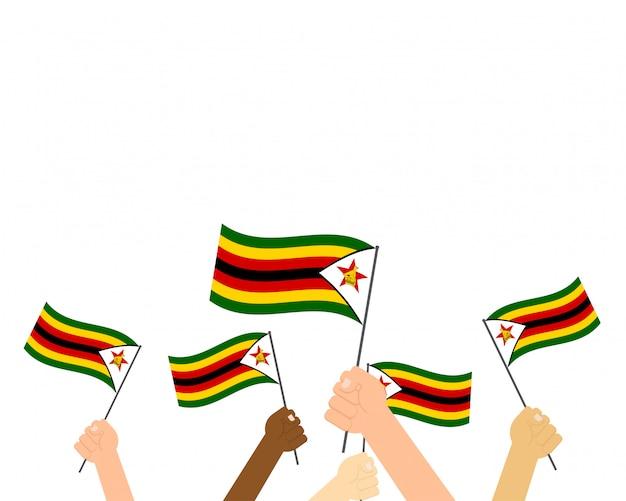 Hände, die simbabwe-flaggen auf weißem hintergrund halten