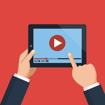 Hände, die tablet-computer mit video-player auf schirm halten