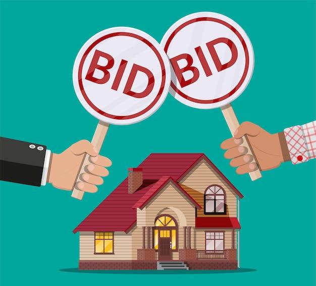 Hände halten auktionspaddel. gebotsteller. immobilien, hausbau.