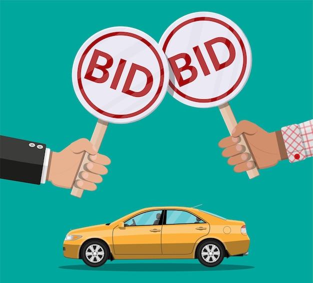 Hände halten auktionspaddel und auto. fahrzeug verkaufen.