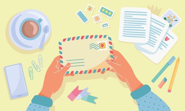 Hände halten umschlag. poststempel, postkarten, stifte, tasse kaffee, handy auf dem tisch. gelber hintergrund, draufsicht. postkreuzung, papierbriefkonzept senden. flache karikaturillustration