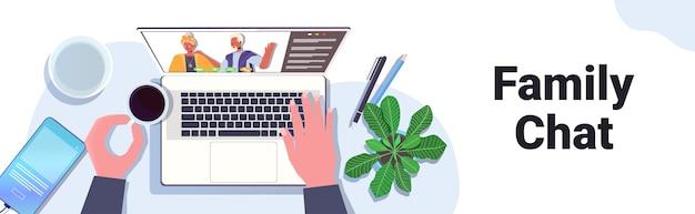 Hände mit laptop-chat mit großeltern während des virtuellen meetings videoanruf familien-chat online-kommunikationskonzept arbeitsplatz desktop top winkel ansicht horizontal