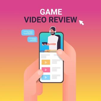 Hände mit smartphone mit blogger auf dem bildschirm mann spieler kommentieren spielprozess video bewertung bloggen live-streaming-konzept porträt online-mobile-app