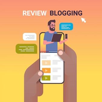 Hände mit smartphone mit technologie-blogger auf dem bildschirm mann testen neue handy-bewertung blogging-konzept vlogger erklärt digitale gadget funktionale porträt online-mobile-app