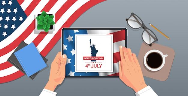 Hände mit tablette mit freiheitsstatue auf dem bildschirm 4. juli amerikanischen unabhängigkeitstag feier konzept arbeitsplatz schreibtisch top winkel ansicht horizontale illustration