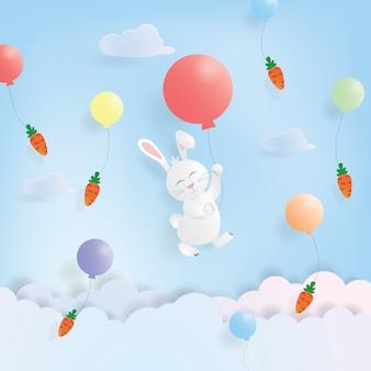 Hängendes kaninchen und karotte ostern-tagesmit buntem ballon im papierschnitt
