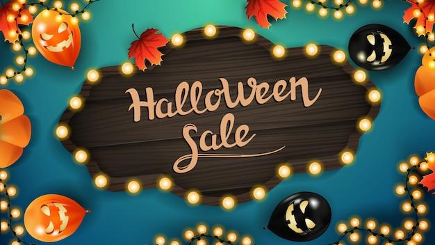 Halloween-verkauf. rabatt-web-banner mit vintage holzbrett, halloween-luftballons, girlanden und herbstlaub auf blauem hintergrund.