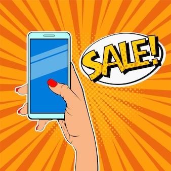 Hand der pop-art frau, die smartphone und beschreibung verkauf hält