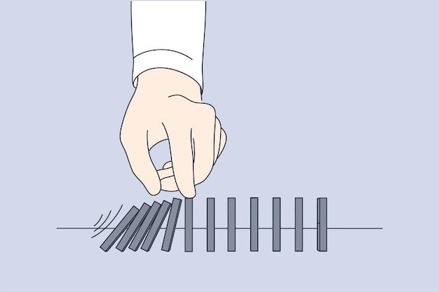 Hand des geschäftsmannführers, der fallende holzblocksteine drückt, die auf tisch gelegt werden
