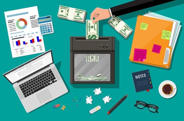 Hand, die dollarbanknote in schreddermaschine setzt. zerstörung kündigung geld schneiden. geld verlieren oder zu viel ausgeben. tisch laptop, taschenrechner, blätter, stift, ringbuch. flaches design der vektorillustration