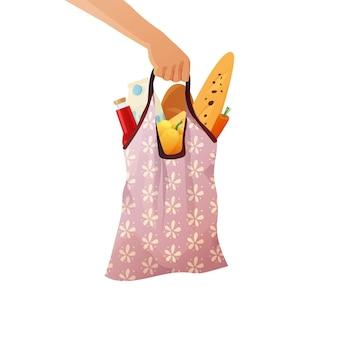 Hand, die eine baumwoll-einkaufstasche von lebensmitteln trägt.