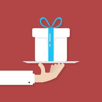 Hand, die große weiße geschenkbox auf platte hält. konzept von weihnachten, bonus, event, crm, zuschuss, dankbarkeit, wunsch, kredit, kurier, rabatt. flache trendgrafikdesign-vektorillustration auf rotem hintergrund