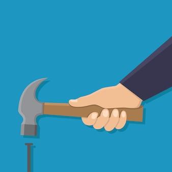Hand, die hammer und einen nagel hält