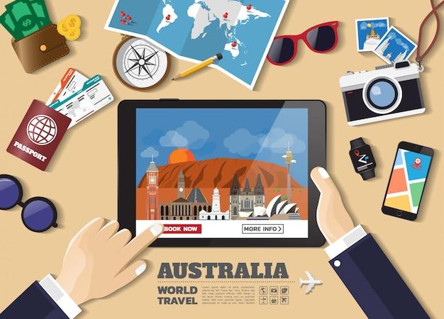 Hand, die intelligentes tablettenbuchungsreiseziel hält berühmte orte australiens
