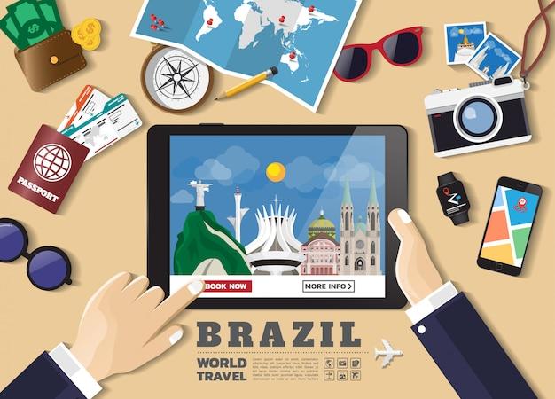 Hand, die intelligentes tablettenbuchungsreiseziel hält berühmte orte brasiliens