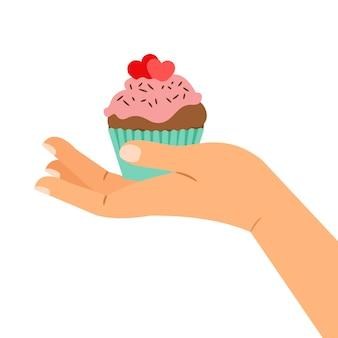Hand, die kleinen kuchen mit zwei herzen hält