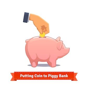 Hand, die münze zu einem rosa sparschwein setzt