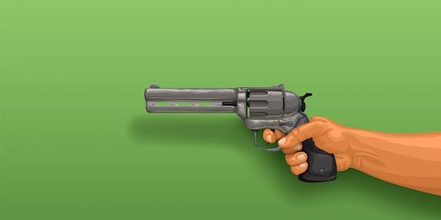 Hand, die revolver auf grün hält